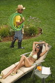 Gardener looking at Hispanic woman sunbathing — Stock Photo