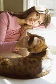 Hispanic woman petting cat — Stock Photo