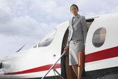 Hispanic businesswoman exiting airplane — Stock Photo