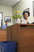 African businesswoman looking at plant — Stock Photo