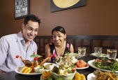 Multi-ethnic couple with table full of food — Stock Photo
