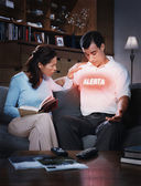 Hispanic woman looking at word on husband's shirt — Stock Photo