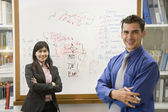 Multi-ethnic businesspeople in front of whiteboard — Stock Photo