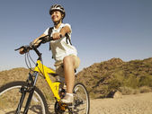 Hispanic woman on bicycle — Stock Photo