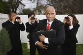 Multi-ethnic businesspeople spying on businessman — Stock Photo