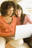 Multi-ethnic women looking at laptop — Stock Photo