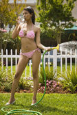 Hispanic woman in bikini watering plants — Stock Photo