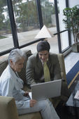 Hispanic businesspeople looking at laptop — Stock Photo