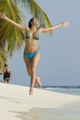 Hispanic woman jumping on beach — Stock Photo