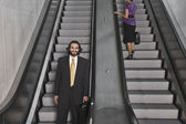 Hispanic businesspeople on escalators — Stock Photo
