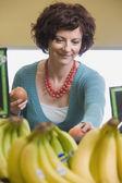Femme, choisir des pommes à l'épicerie — Photo