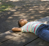 African American girl laying on picnic table — Stock Photo