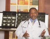 African American male doctor in front of MRIs — Stock Photo