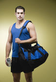 Hispanic man carrying gym bag — Stock Photo