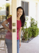 Eurasian woman opening door — Stock Photo