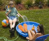 Multi-ethnic couple next to kiddie pool — Stock Photo