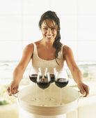 Hispanic woman carrying tray of wine glasses — Stock Photo