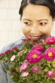 Asian woman holding flowers — Stock Photo