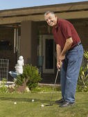 Senior Hispanic man practicing golf — Stock Photo