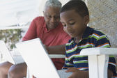 African American grandfather and grandson looking at laptop — Stock Photo