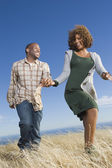 African American couple funning in field — Stock Photo