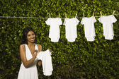 Hispanic woman hanging baby clothing clothes — Stock Photo