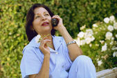 Senior Hispanic woman talking on telephone — Stock Photo