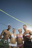 Multi-ethnic friends under beach volleyball net — Stock Photo