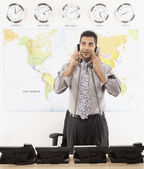 Indian businessman talking on two telephones — Stock Photo