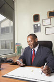 African businessman looking at electronic organizer — Stock Photo
