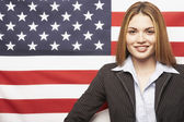 Hispanic businesswoman in front of American flag — Stock Photo