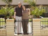 Senior Hispanic couple in front of house — Stock Photo