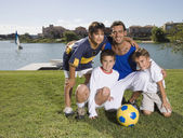 Hispanic father and sons with soccer ball — Stock Photo