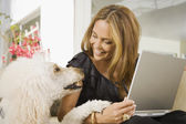 Hispanic woman smiling at dog — Stock Photo