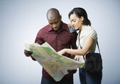 Multi-ethnic couple looking at map — Stock Photo