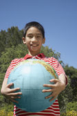 Asian boy holding globe — Stock Photo