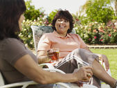 Hispanic women sitting in deck chairs — Stock Photo