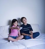 Hispanic brother and sister watching television — Stock Photo