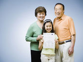 Asian grandparents and granddaughter with school paper — Stock Photo