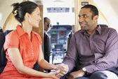 Multi-ethnic couple on airplane — Stock Photo