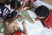 Multi-ethnic students looking at world map — Stock Photo