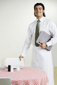 Mixed Race waiter next to table — Stock Photo