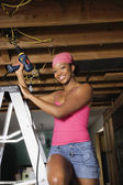 African woman on ladder using drill — Stock Photo