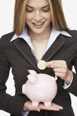 Hispanic businesswoman putting coin in piggy bank — Stock Photo