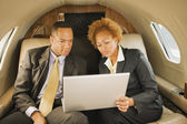 African American businesspeople on airplane — Stock Photo