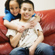Asian siblings hugging on sofa — Stock Photo