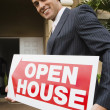 Hispanic real estate agent holding Open House sign — Stock Photo