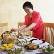 Senior Asian woman setting food on table — Stock Photo