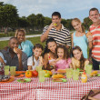 Multi-ethnic friends eating at picnic table — Stock Photo