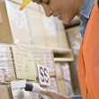 Hispanic warehouse worker scanning shipment — Stock Photo